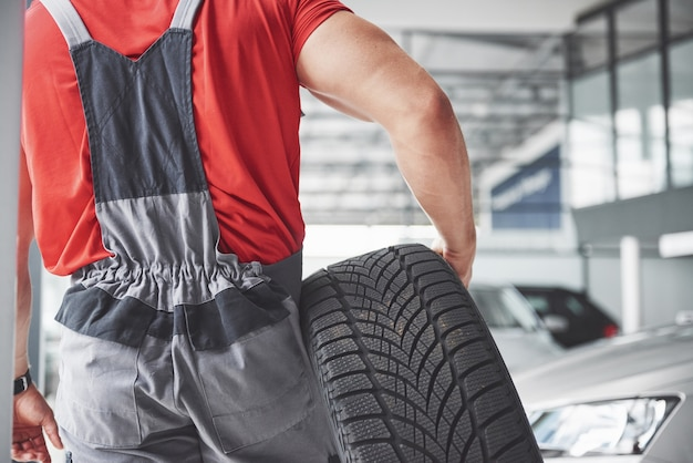 Mechanic holding a tire tire at the repair garage. replacement of winter and summer tires. Free Photo