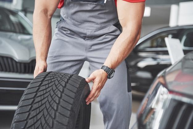 Meccanico in possesso di un pneumatico pneumatico presso il garage di riparazione. sostituzione di pneumatici invernali ed estivi. Foto Gratuite
