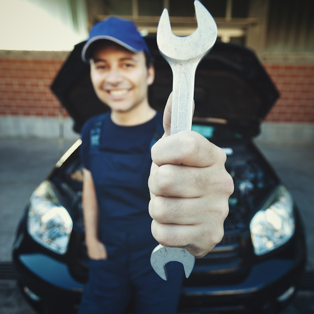 Mechanic holding a wrench at a car garage Premium Photo