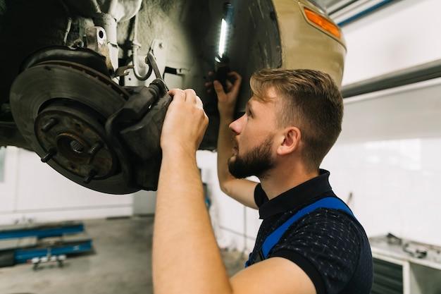 Mechanic inspecting wheel system Free Photo