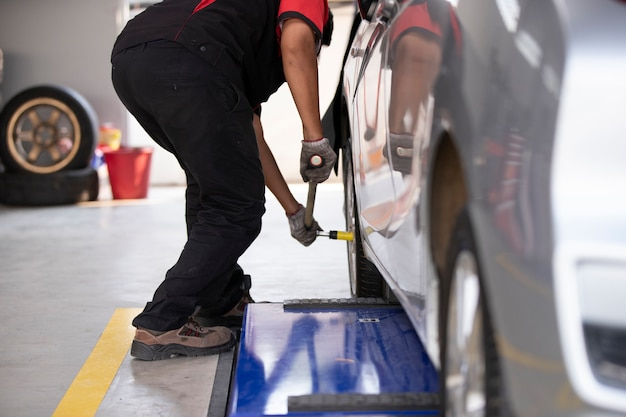 The mechanic is changing the car tires for those who use the tire center. Premium Photo