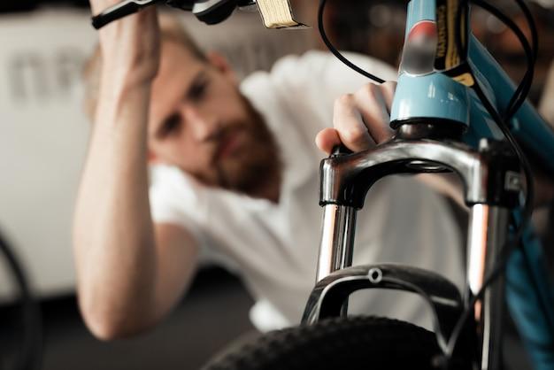 Mechanic looks at cycle details in bike workshop. Premium Photo