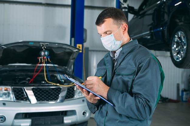 Механик ведет запись об автомобиле в буфер обмена в ремонтной мастерской. Premium Фотографии