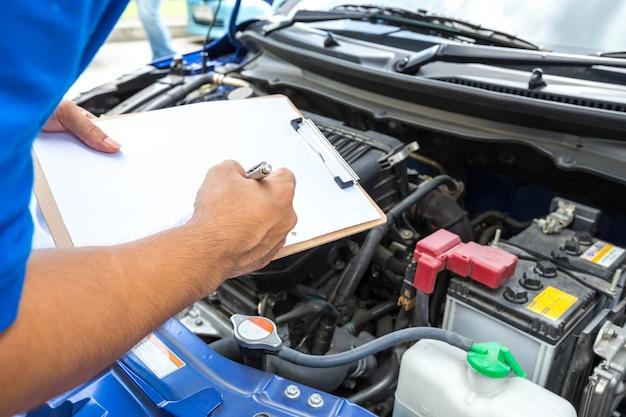 クリップボードを保持し、車をチェックするメカニックの男 Premium写真