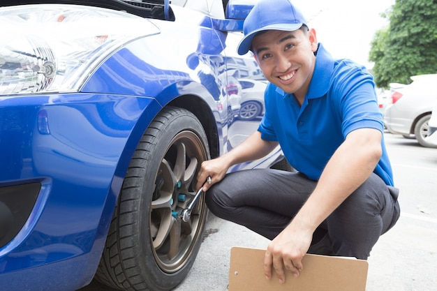 Mechanic man holding clipboard and check the car Premium Photo