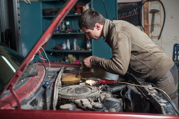 Mechanic man worker pouring antifreeze in the cooling system Premium Photo