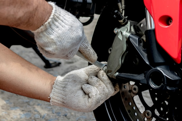 A mechanic people use hand are repairing a motorbike Premium Photo