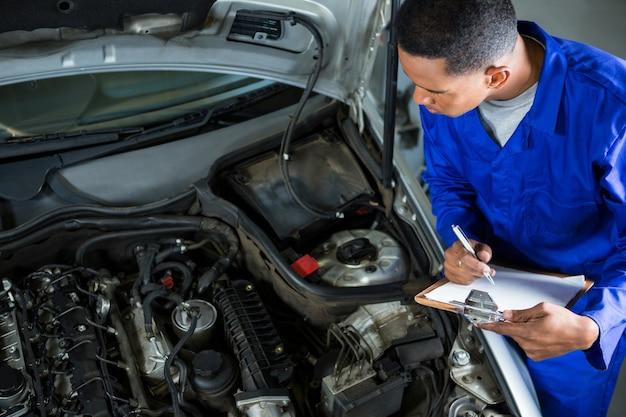 Mechanic preparing a check list Free Photo