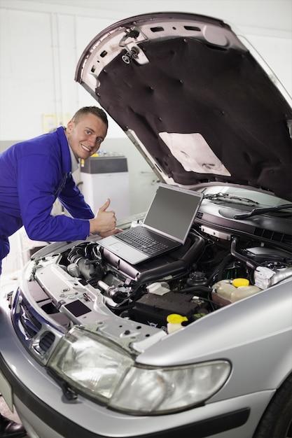 Mechanic repairing a car with a computer Premium Photo