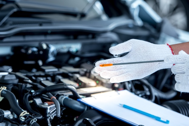 Mechanic repairing car with open hood Premium Photo