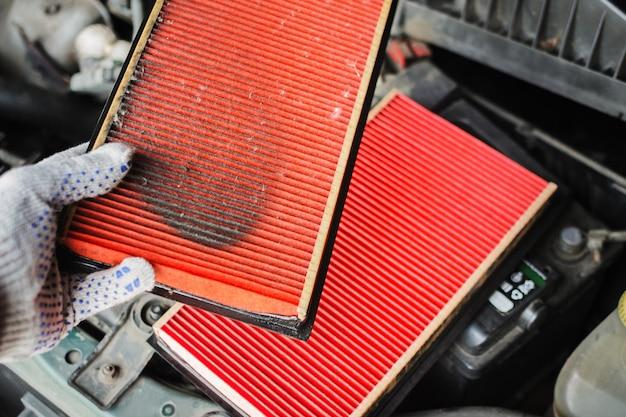 Mechanic replaces air filter in the car Premium Photo