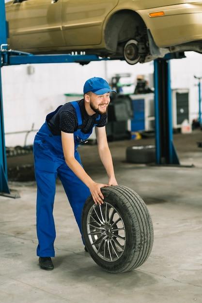 Mechanic rolling wheel to car elevator Free Photo