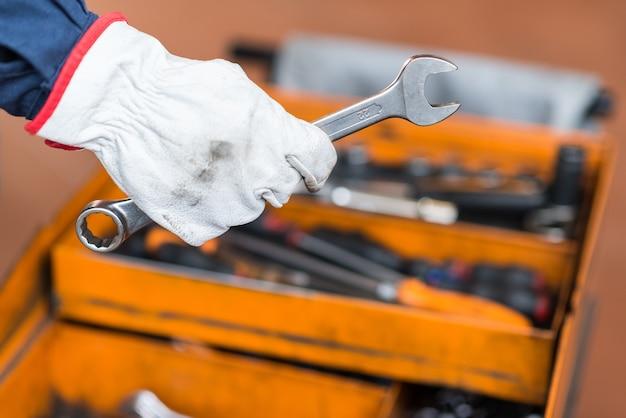 Mechanic's hand holding a wrench Premium Photo