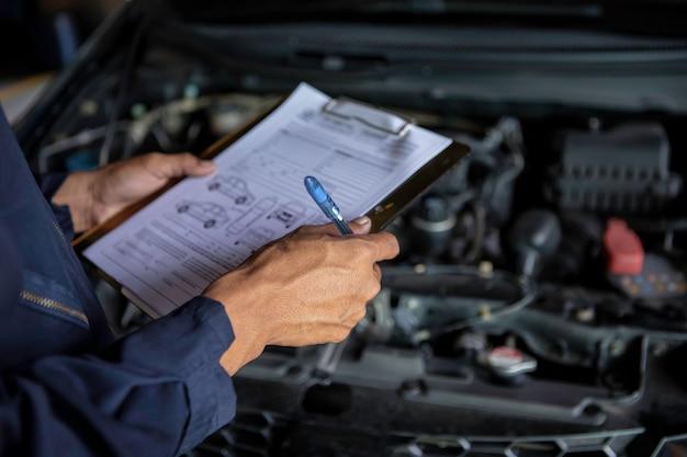 A mechanic service car in garage is check a list cars. Premium Photo