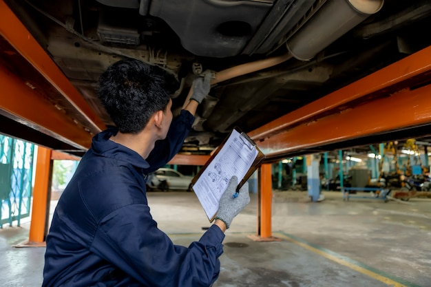 A mechanic service car in garage is check a list cars. Premium Photo