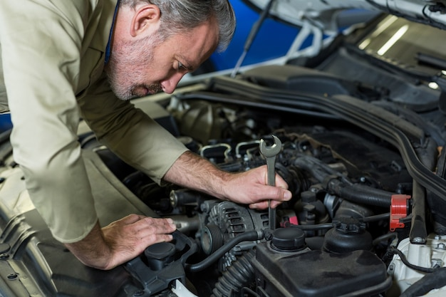 Mechanic servicing a car engine Free Photo
