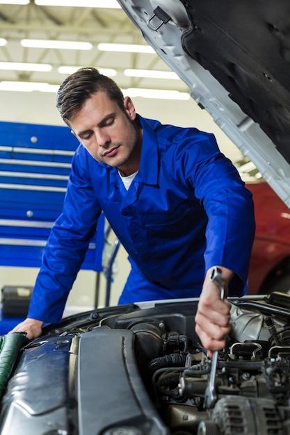Meccanico manutenzione di un motore di un'auto Foto Gratuite