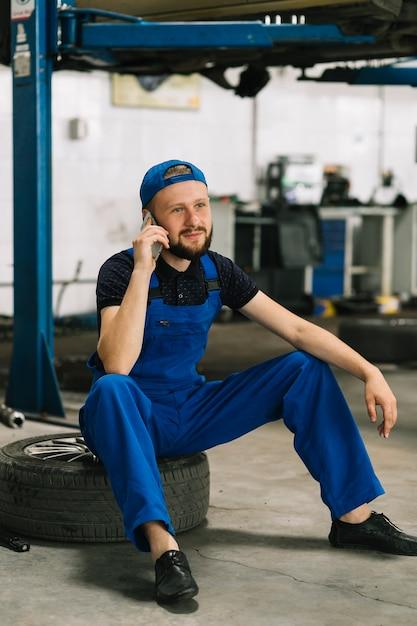 Mechanic using phone on wheelat workshop Free Photo