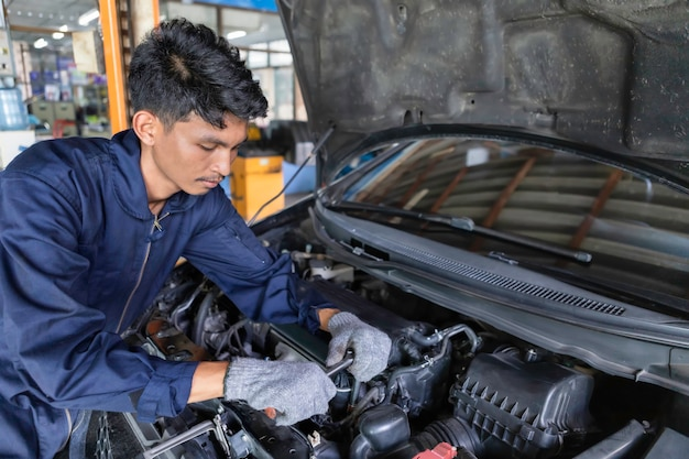 Mechanic using a wrench and a screwdriver to work Premium Photo