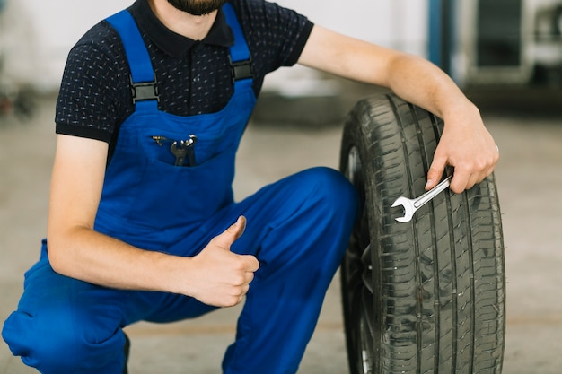 Mechanic with wheel at workshop Free Photo