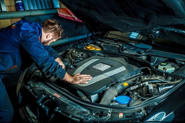 Mechanic working in car motor. auto repair, service center. Premium Photo