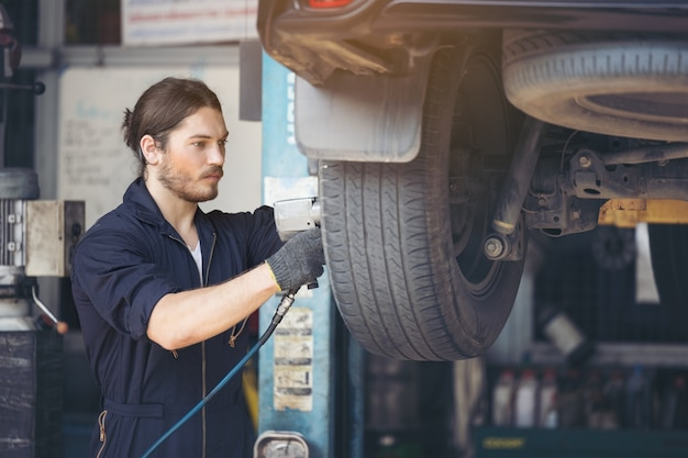 Mechanics fixing car tires at garage Premium Photo