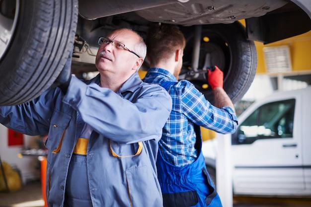 Mechanics repairing a car in the workshop Free Photo