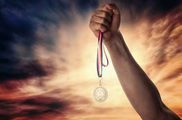 Medal for first place in the athlete's hand against a dramatic sky Premium Photo