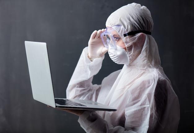 ラップトップコンピューターでウイルスに対する防護服を着ているメディック女性 Premium写真