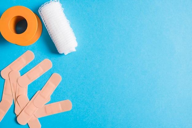 Medical bandage with sticking plaster and cotton gauze bandage on blue background Free Photo