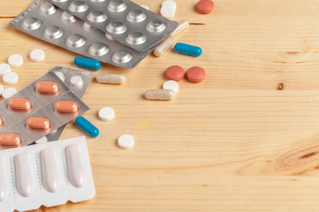 Medical colorful pills, capsules or supplements for the treatment and health care on wooden background Premium Photo
