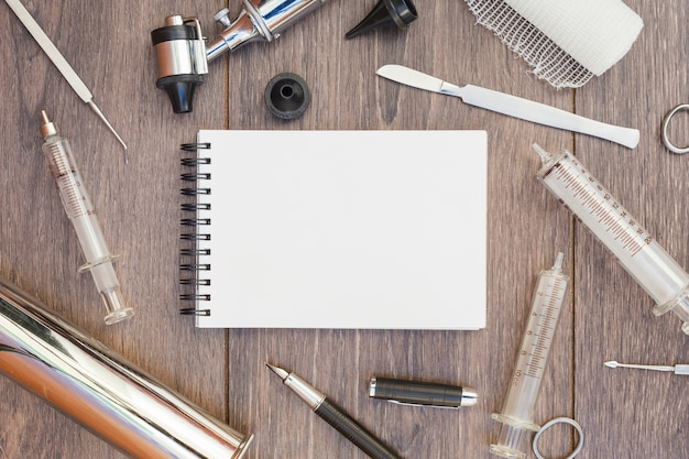 Medical equipment's surrounded around the blank spiral notepad on wooden desk Free Photo