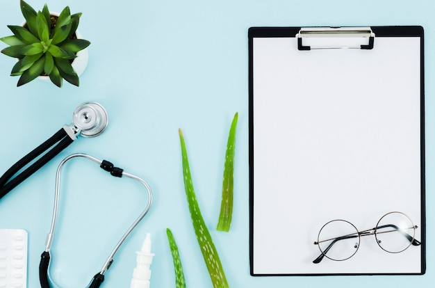 Medical equipment's with aloe vera leaves near the white paper on clipboard on blue background Free Photo