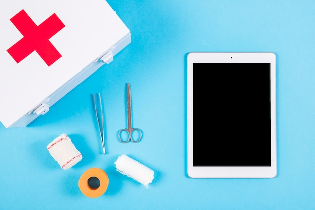 Medical equipments with first aid kit and blank digital tablet on blue background Free Photo