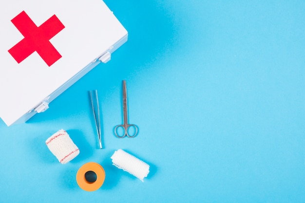 Medical equipments with first aid kit on blue background Free Photo