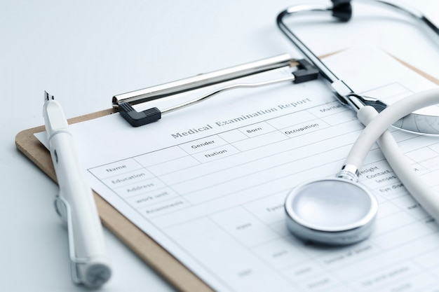 Medical examination report and stethoscope on white desktop Free Photo