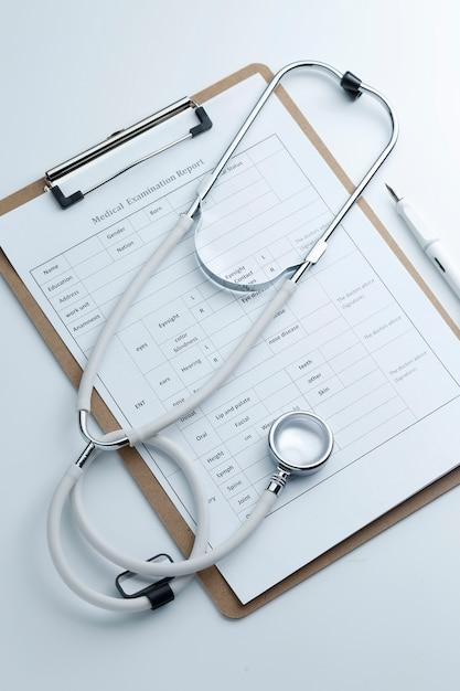 Medical examination report and stethoscope on white desktop Free Photo