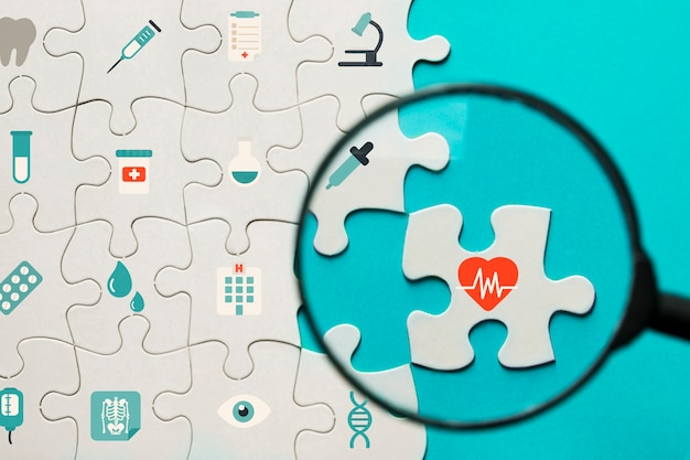 Medical icons puzzle with magnifying glass Premium Photo