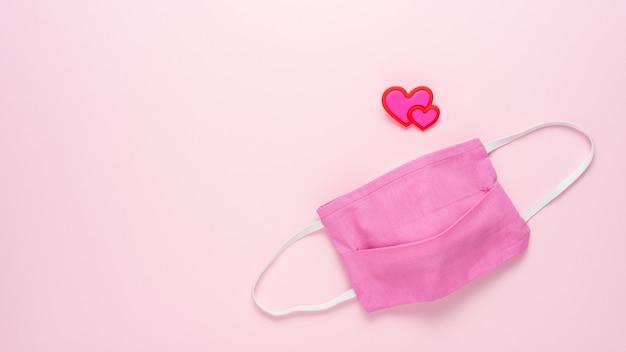 ピンクの表面にハートのある医療用マスク。 Premium写真