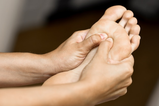 Medical massage at the foot in a physiotherapy center. Free Photo