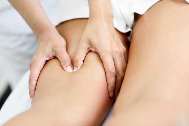 Medical massage at the leg in a physiotherapy center. Free Photo