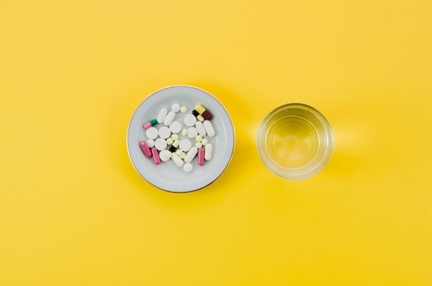 Medical pills in bowl and glass water on yellow background Free Photo