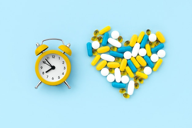 블루에 알람 시계와 함께 심장 모양의 의료 약 프리미엄 사진