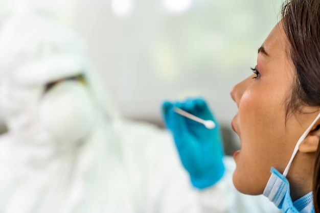 Medical staff do covid-19 testing by throat swab to asian woman Premium Photo