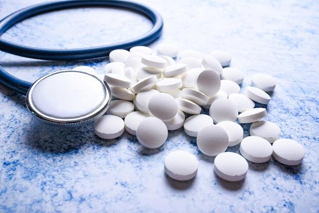 医療聴診器と多くの白い錠剤青い表面。循環器のコンセプト Premium写真