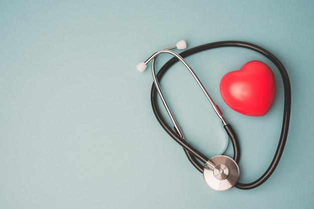 Медицинский стетоскоп и красное резиновое сердце на синем фоне, вид сверху Premium Фотографии