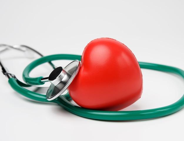 Медицинский стетоскоп и красное резиновое сердце на белом фоне, крупным планом Premium Фотографии