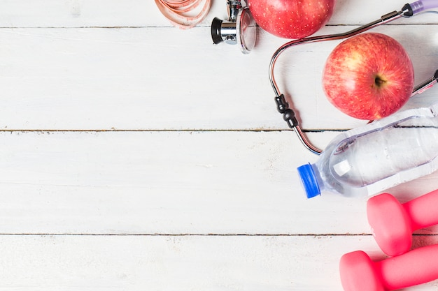 Medical stethoscope and an apple fruit over wooden background. healthy lifestyle concept image. Free Photo