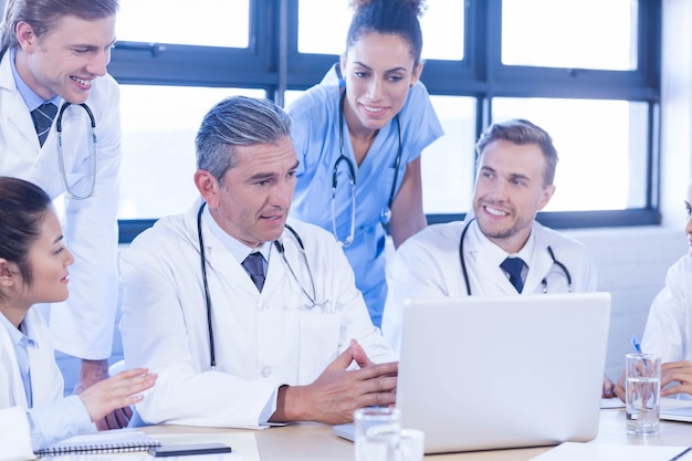 Medical team looking into laptop and having a discussion at conference room Premium Photo