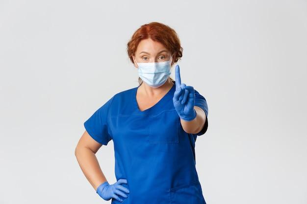 Медицинские работники, пандемия, концепция коронавируса. серьезная профессиональная женщина-врач, медсестра в маске и перчатках, предупреждающая людей, трясущая пальцем в запрете. Premium Фотографии